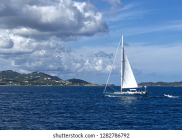 Sailboat towing dingy against blue sky with fluffy clouds