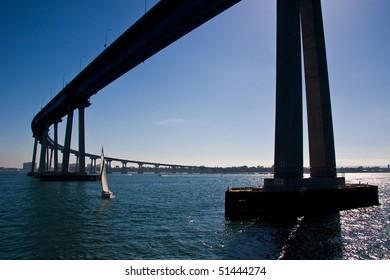 A sailboat under the San Diego - Coronado Bridge.
