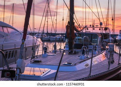 Sailboat with wooden deck standing in marine at beautiful sunset