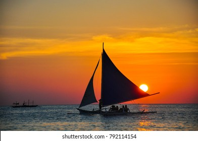 Sailboats against beautiful sunset in Boracay, Philippines.
