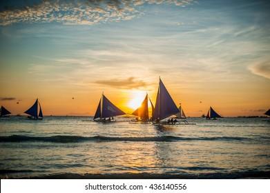 Sailboats with blue sails at sunset, Boracay Island