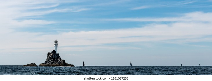 Sailboats circling Fastnet Lighthouse