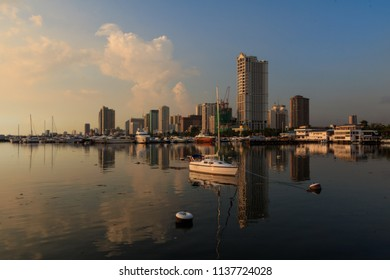 Sailboats In City By Buildings Against Sky During Sunset