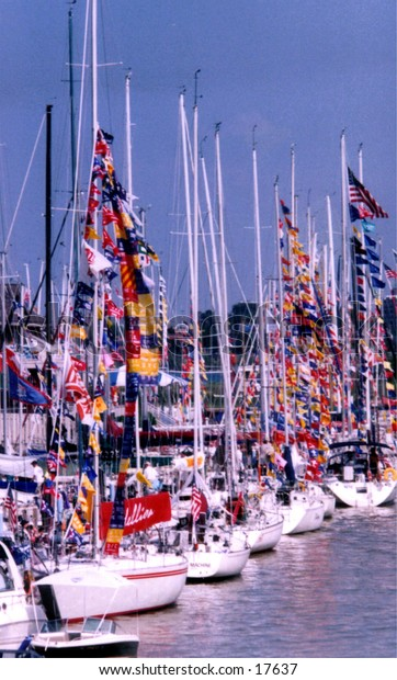 Sailboats, with colorful flags, docked along the river.