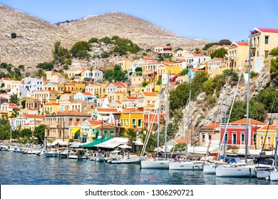 Sailboats and colorful neoclassical houses in harbor town of Symi (Symi Island, Greece)