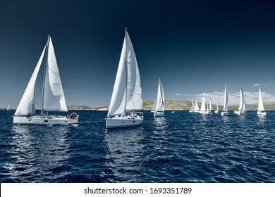 Sailboats compete in a sail regatta at sunset, race of sailboats, reflection of sails on water, multicolored spinnakers, number of boat is on aft boats, Bright colors