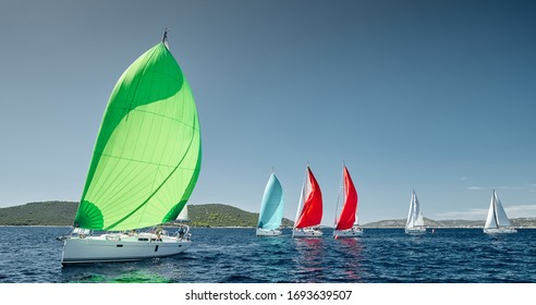Sailboats compete in a sail regatta at sunset, race of sailboats, reflection of sails on water, multicolored spinnakers, number of boat is on aft boats, island is on background, clear weather