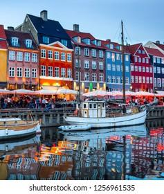 Sailboats moored by Nyhavn promenade illuminated at the evening, Copenhagen old town cityscape, Denmark