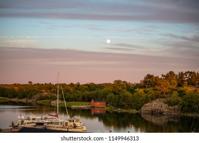 Sailboats moored at the inlet at Kökar, a municipality of the Åland Islands, Finland, a few minutes before sunset, a few days after midsummer, and two days before the full moon.