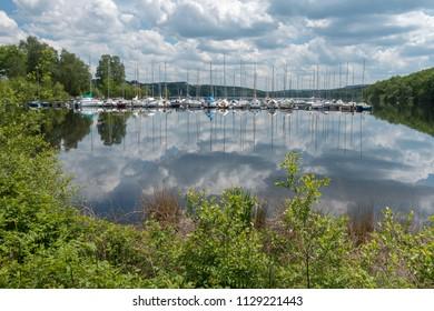 Sailboats moored at a jetty on Lake Vassivière, France