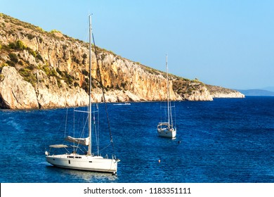 Sailboats moored at the rocky coast of Croatia. Evening bay on the island of Hvar. Relax in the sea. Ships at sunset. Holidays on a sailboat