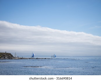 Sailboats passing Clover Point, Straits of Juan de Fuca, Victoria, British Columbia, Canada.  Cloud bank behind scene, blue and white sails, figures standing on point