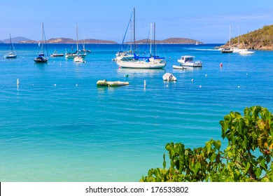 Sailboats and power boats anchored in crystal clear turquoise waters in the Caribbean
