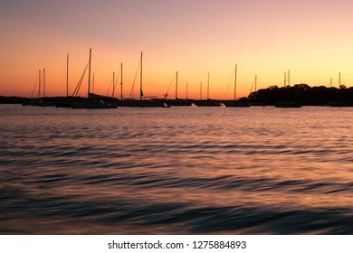 Sailboats return to harbor as a beautiful sunset signals the end of the day, on Key Biscayne, near Miami, Florida.