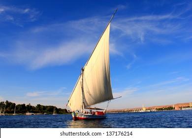 Sailboats sliding on Nile river. Felluca (traditional boat) of Egypt in Aswan's sunset.
