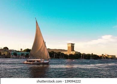 Sailboats sliding on Nile river, Egypt. Felluca (traditional boat) of Egypt in Aswan's sunset.