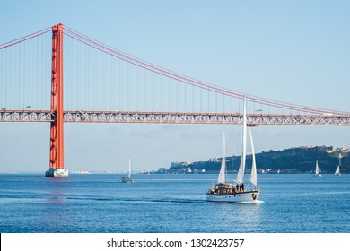 Sailboats with white sails on the Tagus River, 25 of April (25 de abril) Bridge, Christ the king elevator tower in the background, Lisbon, Portugal