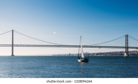 Sailboats with white sails on the Tagus River, 25 of April Bridge, Lisbon, Portugal.