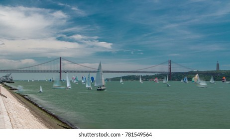 Sailfishes on the Tagus river with 25th of April Suspension Bridge on background, connecting Almada and Lisbon in Portugal with cloudy blue sky wide angle lens