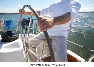 sailing, age, tourism, travel and people concept - close up of senior man steering wheel and navigating sail boat or yacht floating in sea