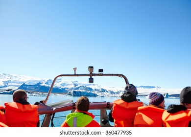 Sailing between icebergs in Jokulsarlon Lagoon, Iceland. Crowd on amphibian tour among melting glaciers.