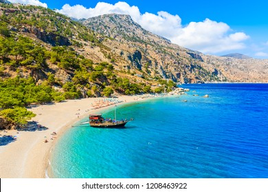 Sailing boat anchoring at beautiful Apella beach on Karpathos island, Greece