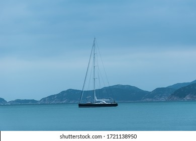 A sailing boat is in the bay which the sea is blue, the sky is blue and the mountain is blue too. Relaxing concept