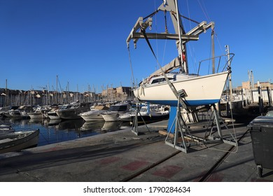 Sailing boat being repaired on a wharf in the old harbor of Marseille, France