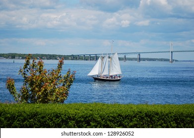 a sailing boat is sailing by newport bridge, rhode island