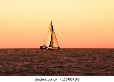 Sailing boat in a calm ocean at sunset