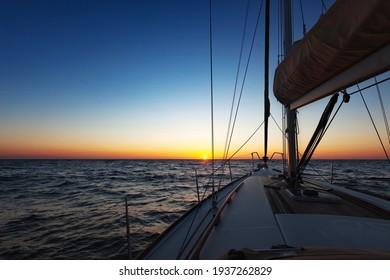Sailing boat at calm open sea at sunset