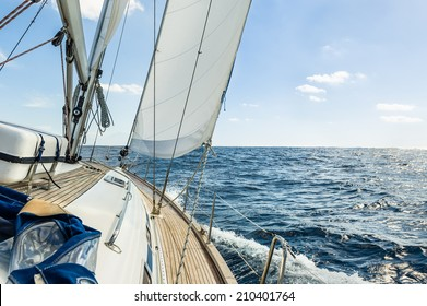 Sailing boat deck with hoisted sails and teak deck