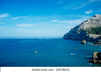 Sailing boat exploring cliffs of Bay of Biscay