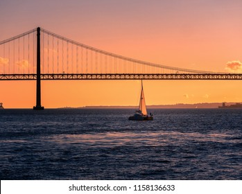 Sailing boat in front of the bridge in Lisbon during sunset. clear sky. sunset scene