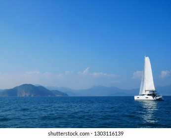 Sailing boat in Hong Kong. A blue gradient from the sky to the ocean, with some amazing mountains on the background.