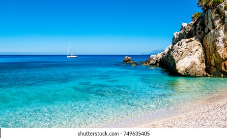A sailing boat into the turquoise Mediterranean Sea, at San Vito Lo Capo, Sicily, Italy.