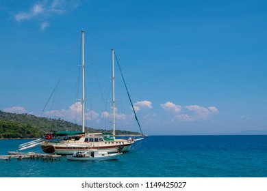 Sailing boat and a little boat docked in a bay