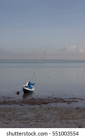 Sailing boat at low tide in Il de Re with big sky.
