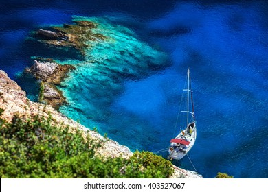 Sailing boat lying in a bay with clear transparent waters, in Polyegos island, Cyclades, Greece