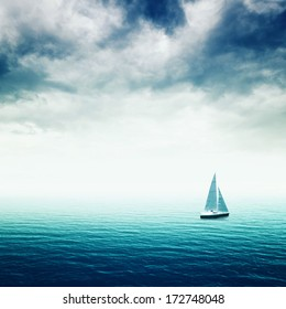 Sailing boat on Blue sea with heavy storm clouds, conceptual image of uncertain future