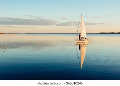 Sailing boat on a calm lake with reflection in the water. Serene scene landscape. Horizontal photograph.