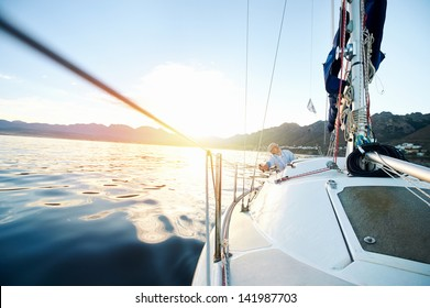 Sailing boat on on ocean water at sunrise with flare and outdoor lifestyle