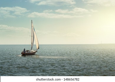 Sailing boat on the open sea at the sunset