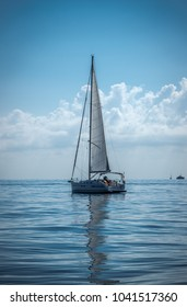 Sailing boat on the sea sails reflect on a calm water summer day dark blue colors