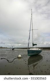 Sailing boat on shore at low tide in Il de Re.