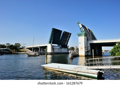 A sailing boat passing under the open drawbridge, West Palm Beach, FL, USA
