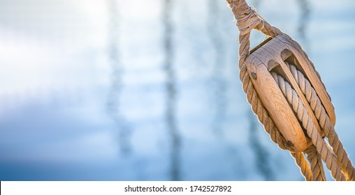 Sailing boat pulley, block and tackle with nautical rope. Nautic water panoramic background.