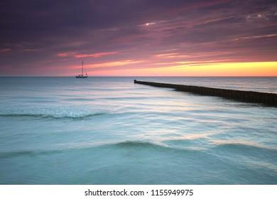 sailing boat at sea - romantic morning light at the beach