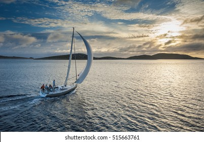 Sailing boat with spinnaker sail on open sea
