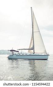 Sailing boat yacht closeup on blue water sea.
